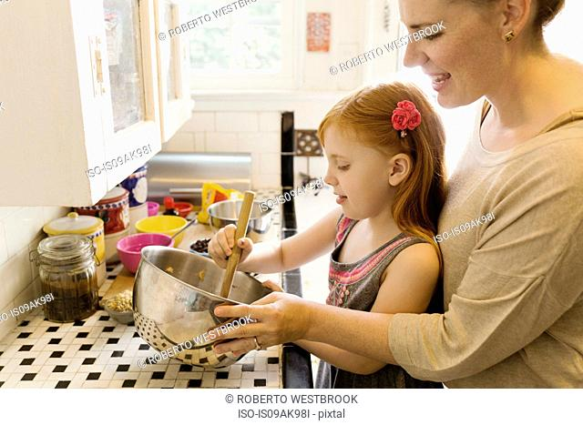 Girl and mother mixing ingredients in bowl in kitchen
