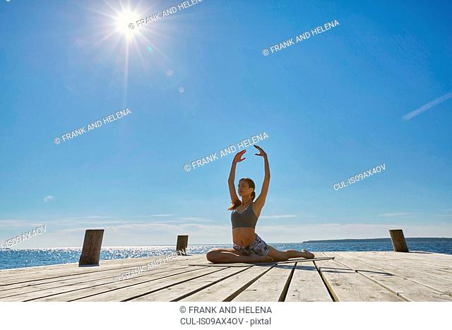 Woman on pier doing the splits arms raised in yoga position