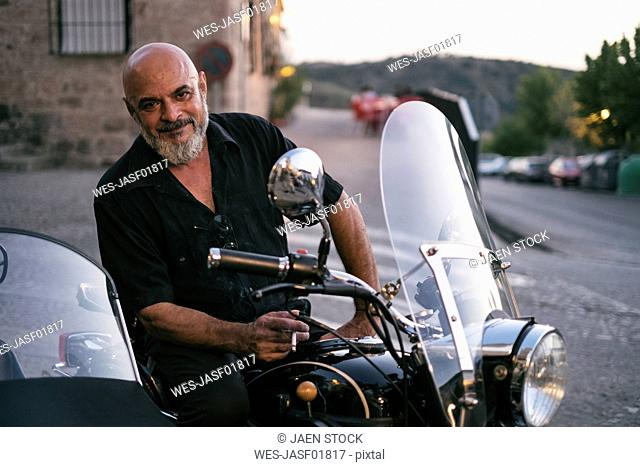 Spain, Jaen, mature man posing on his motorcycle with a sidecar while smoking