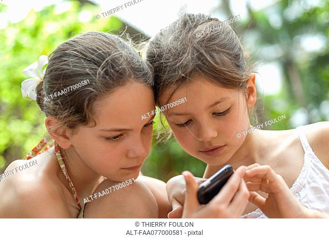 Sisters looking at cell phone together