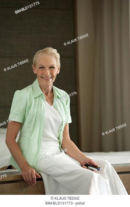Senior Caucasian woman sitting on bed
