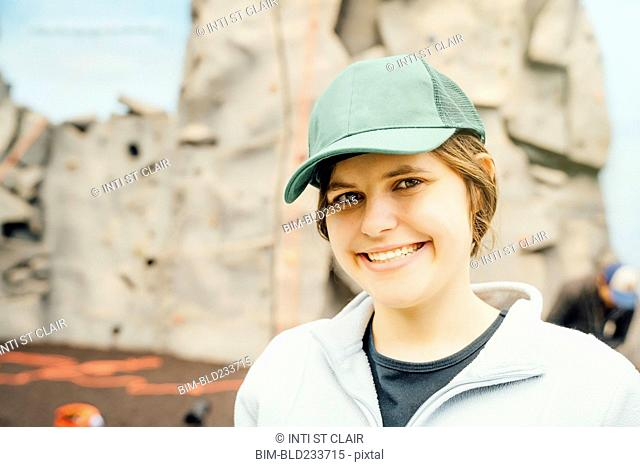 Caucasian woman smiling near rock climbing wall