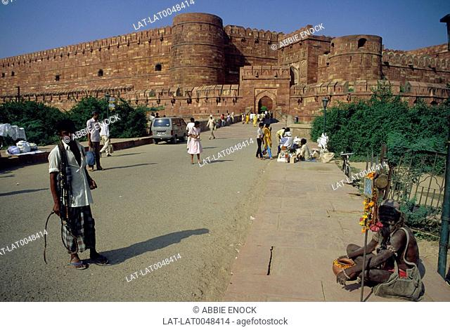 The walls of the large red sandstone hilltop fort. Agra fort,an entrance gate and beggars and people at souvenir stalls on the road