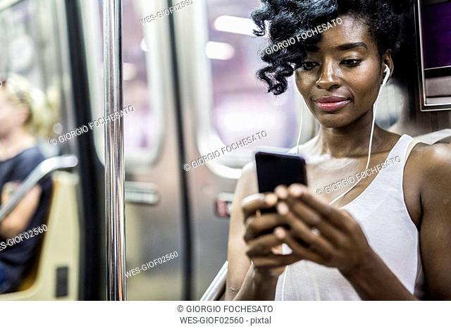 Portrait of woman looking at cell phone in underground train