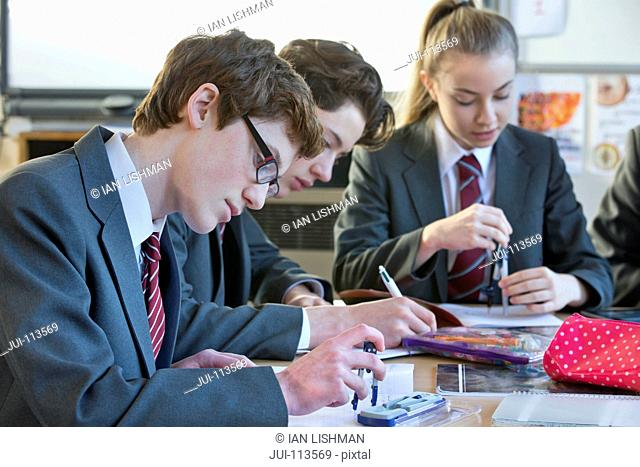 High school student doing math homework with drawing compass