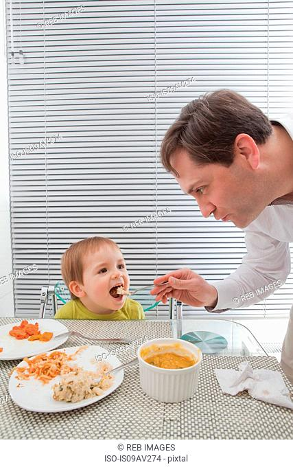 Father feeding son at dining table