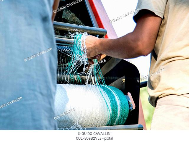 Cropped shot of two male farmworkers untangling netting in hay baler