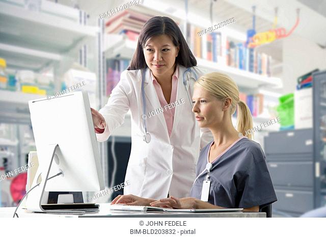 Doctor and nurse working at computer in hospital