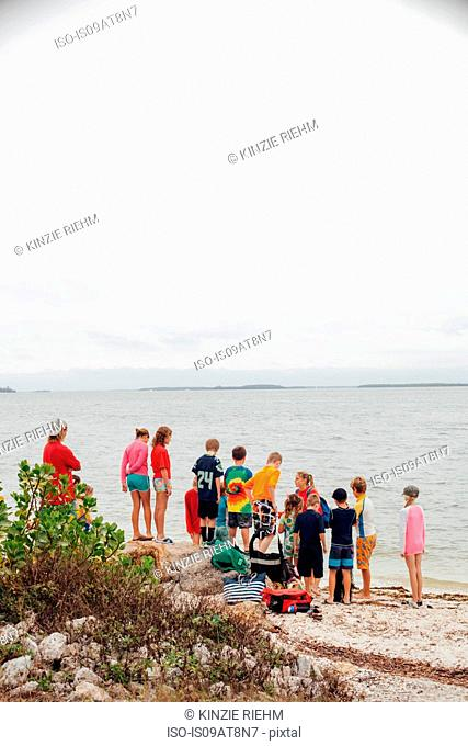 Rear view of large group of children on beach, Sanibel Island, Pine Island Sound, Florida, USA
