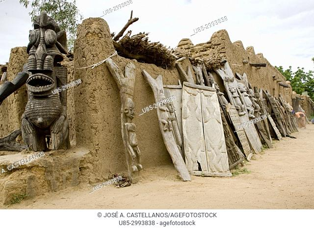 Dogon Country. Mali. Ende Village. On the left there is a large carving and on its right several wooden pillars and beautifully carved doors with Dogón...
