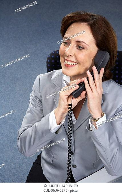Mature businesswoman on phone, smiling