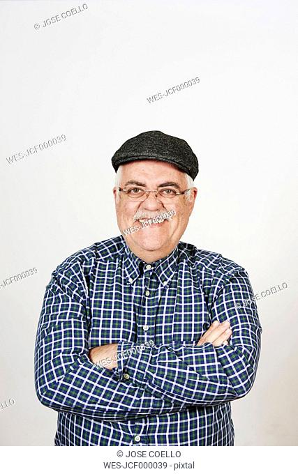Portrait of smiling senior man with arms crossed in front of white background