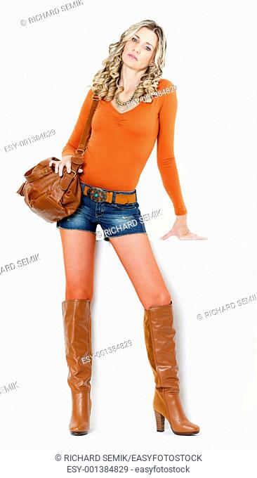 standing woman wearing fashionable brown boots with a handbag