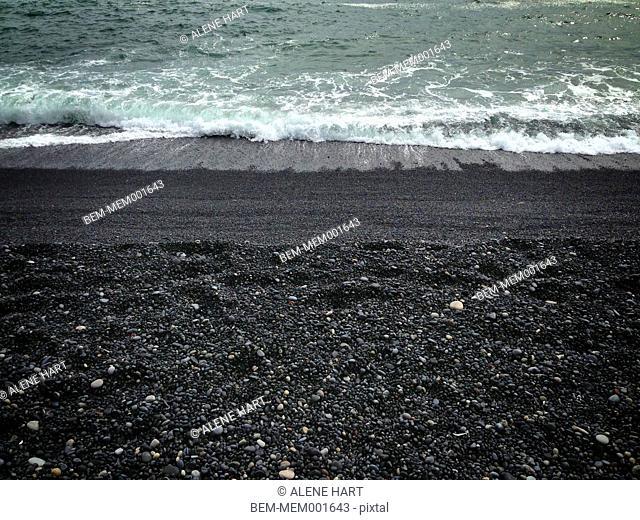 Waves washing up on black sandy beach
