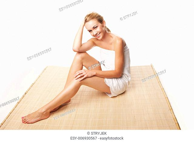 Gorgeous blonde woman wrapped in a towel sitting on a reed mat with long shapely legs and a beautiful smile as she relaxes after a beauty treatment