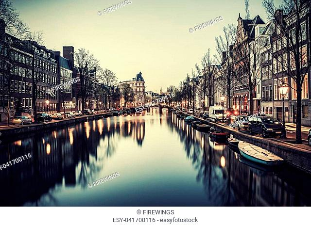 Evening in Amsterdam, night vintage cityscape with buildings and river. Film filter