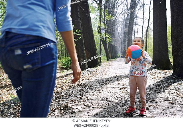 Mother and daughter playing ball in a park