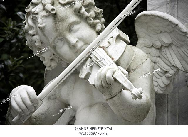 angle statue playing violin, tombstone on graveyard