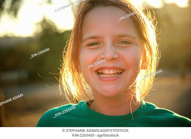 Young happy girl smiling at the camera on a camping trip