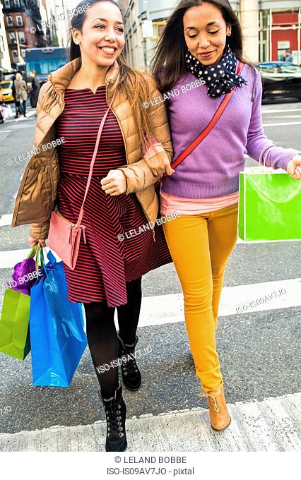 Young female adult twins with shopping bags crossing city road