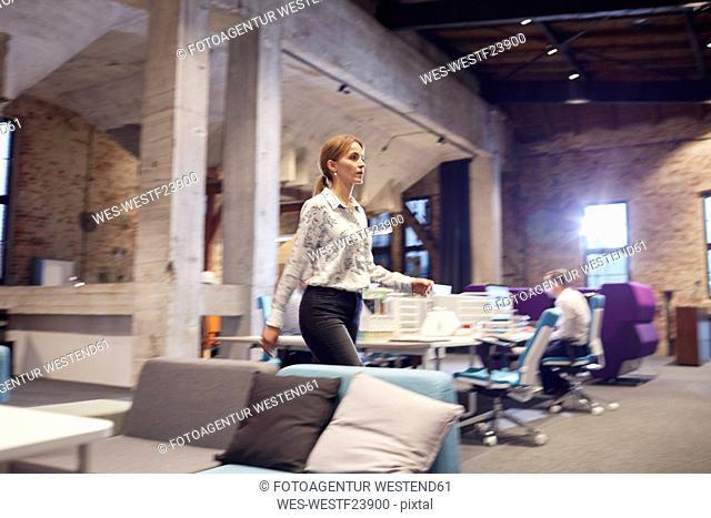 Busy woman walking in modern office, blurred motion