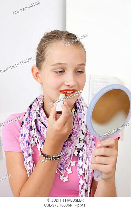Smiling girl applying lipstick in mirror