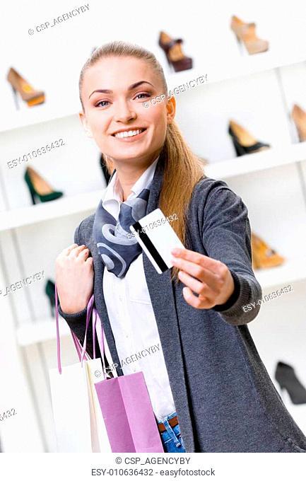 Girl showing credit card in footwear shop