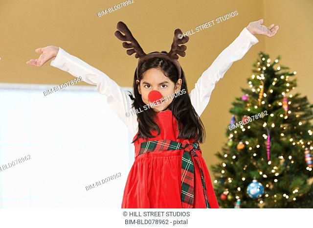 Hispanic girl wearing reindeer nose and antlers