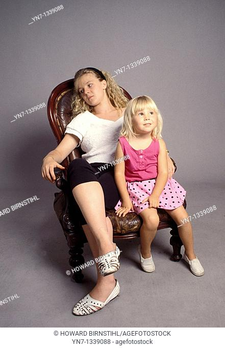 mother and daughter relaxing on an old armchair