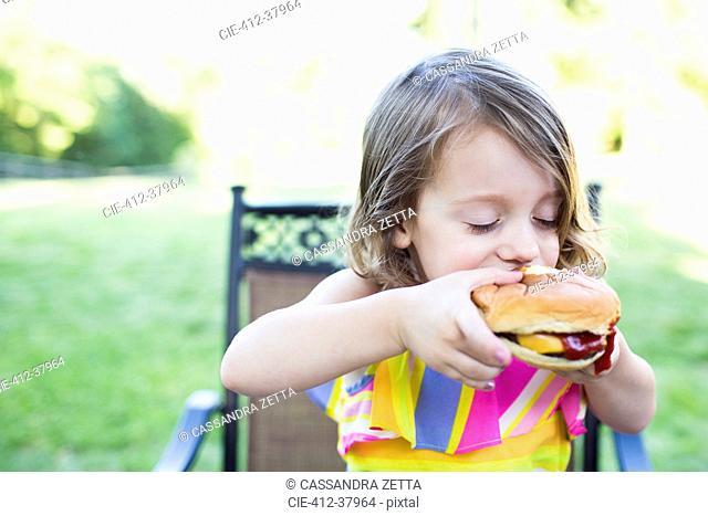 Preschool girl eating messy cheeseburger on patio
