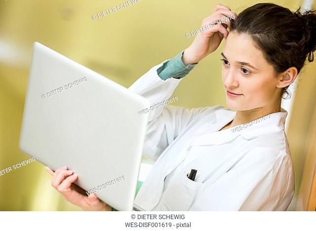 Teenage girl in doctor's overall with laptop