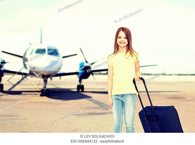 tourism, holiday, vacation, childhood and transportation concept - smiling little girl with travel bag over airport background