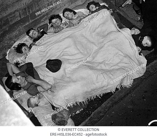 World War 2, Battle of Britain. A woman and eight children share a blanket in a southeast London subway station bomb shell during the Blitz. Ca