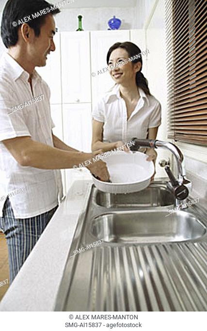 Couple in kitchen, man washing dishes, woman standing next to him, smiling