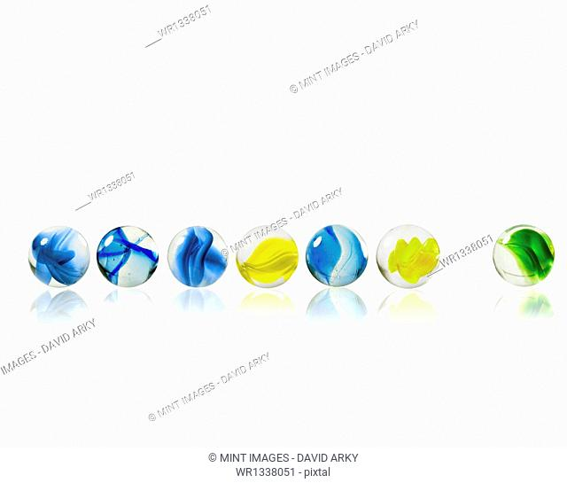 A row of glass marbles of different patterns and colours, with one separated from the rest