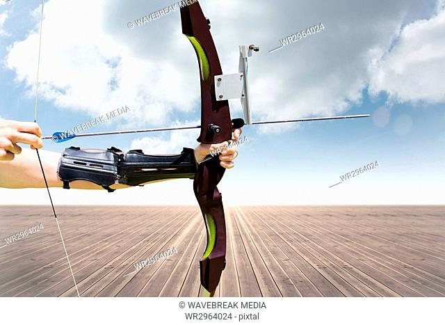 Part of archery player with desert and blue sky background