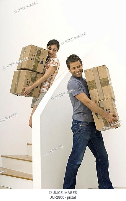 Couple carrying boxes down staircase, moving house, smiling