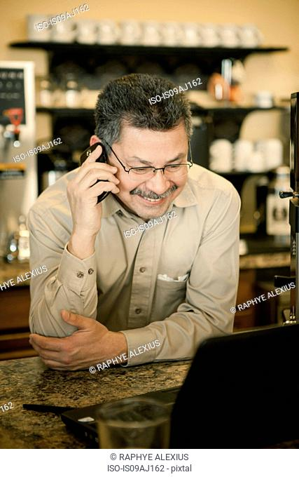 Mature male cafe owner chatting on smartphone at cafe counter