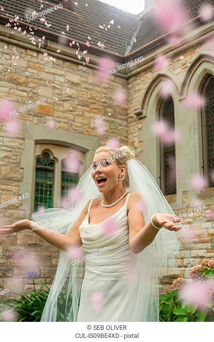 Bride catching confetti outside church