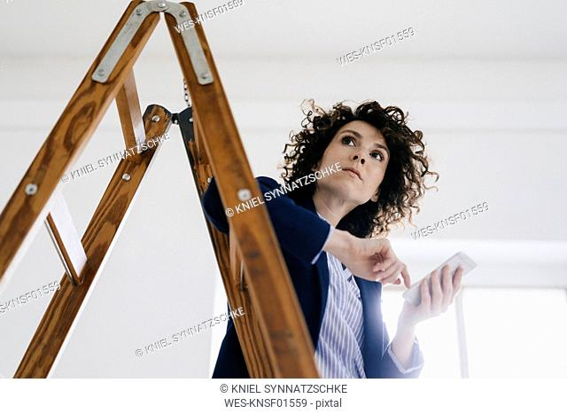 Businesswoman standing by ladder in office, holding smartphone