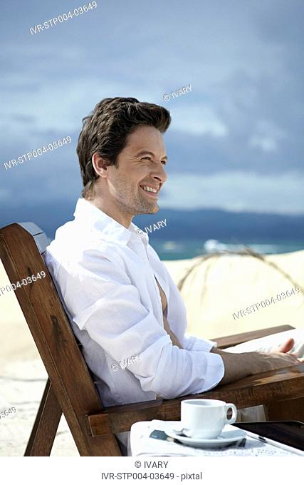 A man posing in a deck chair at a resort
