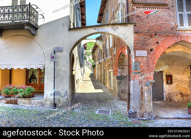 Narrow paved street along vintage brick houses in town of Avigliana, northern It