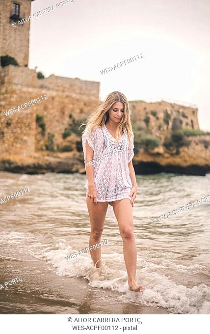 Beautiful young woman wading in water on the beach