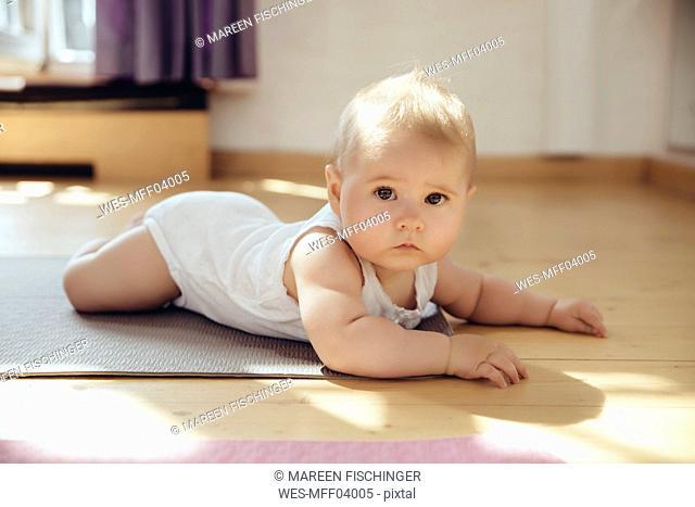 Portait of baby lying on yoga mat