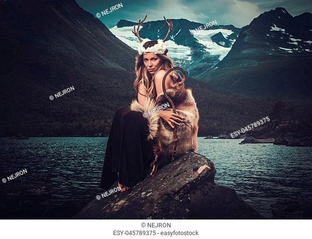 Nordic goddess in ritual garment near wild mountain lake in Innerdalen valley, Norway