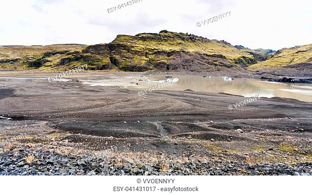 travel to Iceland - melting snow in water from Solheimajokull glacier (South glacial tongue of Myrdalsjokull ice cap) in Katla Geopark on Icelandic Atlantic...