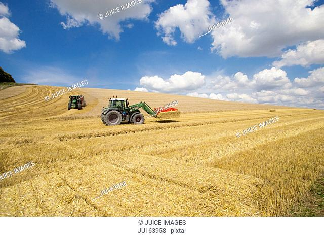 Tractors baling and stacking straw bales in sunny rural field