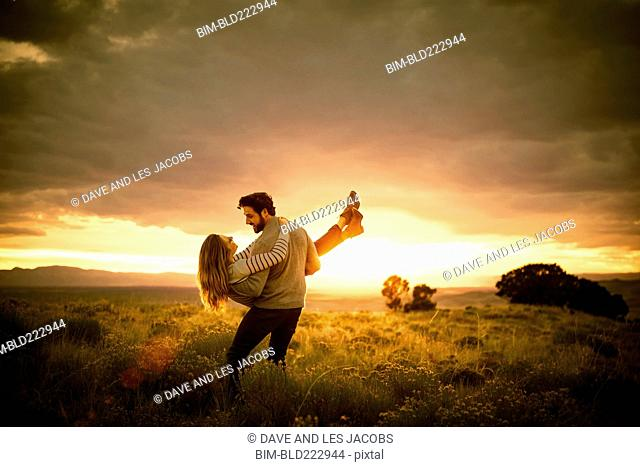 Hispanic man carrying woman in field at sunset