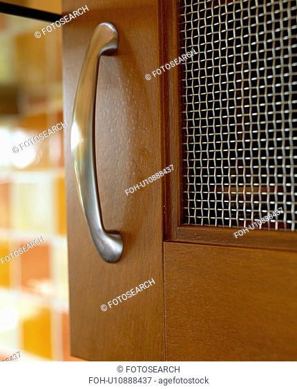 Close-up of steel handle and mesh panel on walnut door