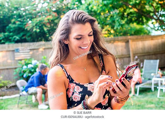 Mid adult woman texting on smartphone at party in garden